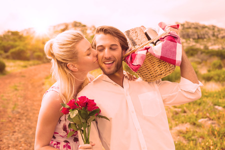 Cute couple going for a picnic with woman kissing boyfriends cheek on a sunny day photo