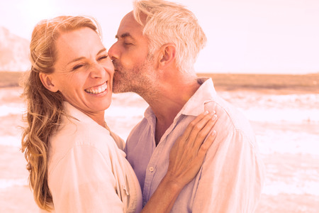escapism: Man kissing his smiling partner on the cheek at the beach on a sunny day