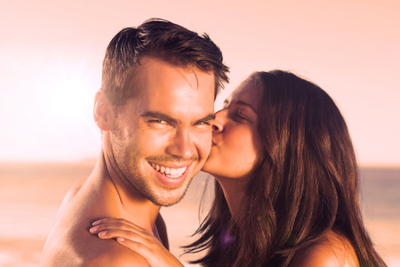 Attractive woman on the beach kissing her boyfriend on the cheek Stock Photo