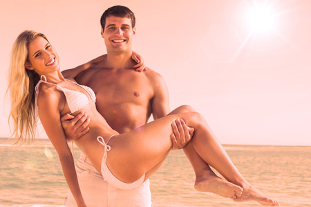 carrying: Man carrying his pretty girlfriend smiling at camera at the beach Stock Photo
