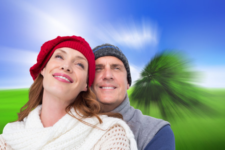 warm clothing: Happy couple in warm clothing against sunny green landscape