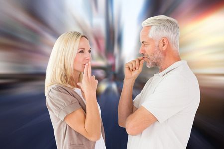 exasperated: Couple staying silent with fingers on lips against blurry new york street Stock Photo