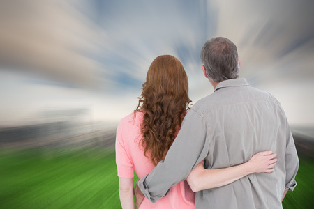 arm around: Casual couple standing arm around against cloudy sky over city