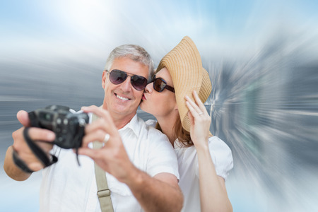 vacationing: Vacationing couple taking photo against room with large window looking on city Stock Photo