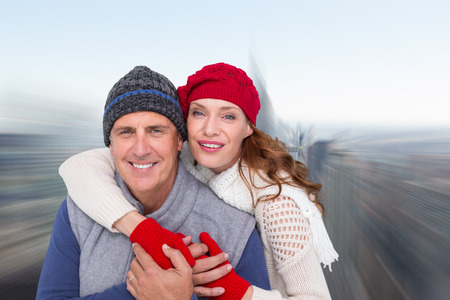 warm clothing: Happy couple in warm clothing against city skyline