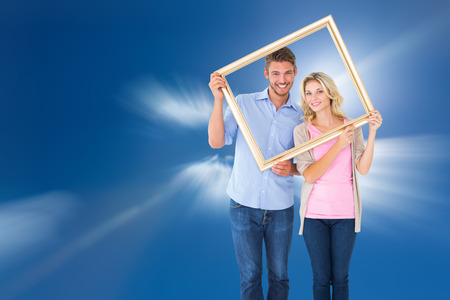 Attractive young couple holding picture frame against bright blue sky with clouds photo