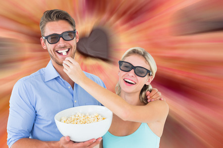 Composite image of happy young couple wearing 3d glasses eating popcorn photo