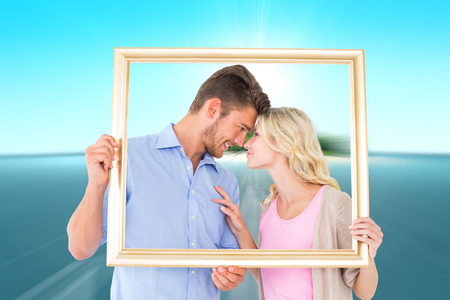 Attractive young couple holding picture frame against tropical island in blue ocean photo