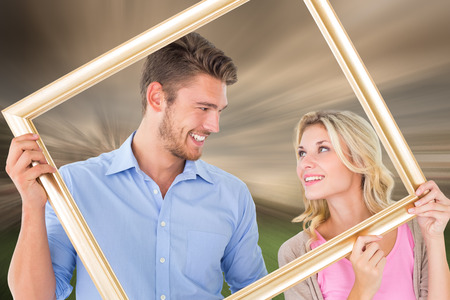 Attractive young couple holding picture frame against sunny day in amsterdam photo