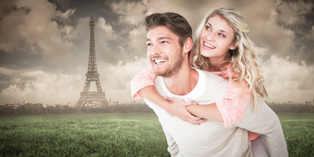 Handsome man giving piggy back to his girlfriend against paris under cloudy sky photo