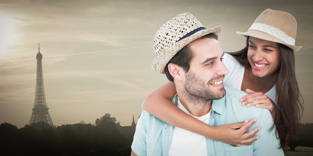 Happy casual man giving pretty girlfriend piggy back against eiffel tower photo