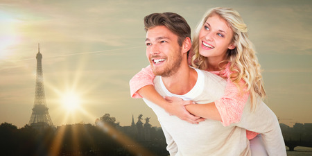 long hair boy: Handsome man giving piggy back to his girlfriend against eiffel tower