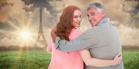 arms around: Casual couple standing arms around against paris under cloudy sky