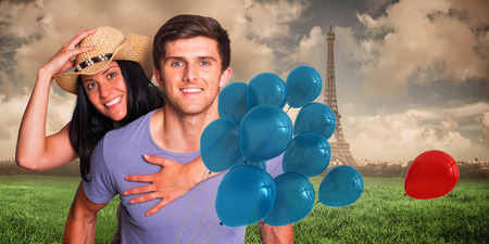 Man giving his pretty girlfriend a piggy back against paris under cloudy sky photo