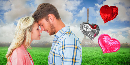 Attractive couple standing touching heads against eiffel tower photo