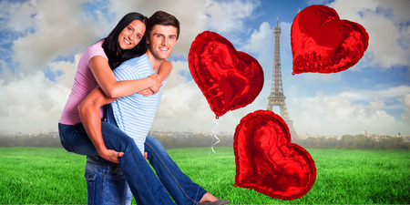 Young man giving girlfriend a piggyback ride against eiffel tower photo