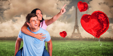 Young man giving girlfriend a piggyback ride against paris under cloudy sky photo