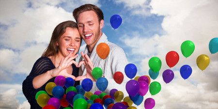 forming: Happy couple forming heart with hands against blue sky with white clouds Stock Photo