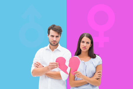 Upset couple holding two halves of broken heart against pink and blue photo