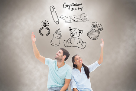 Cute couple sitting with arms raised against grey background with vignette photo
