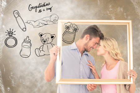 its a boy: Attractive young couple holding picture frame against congratulations its a boy