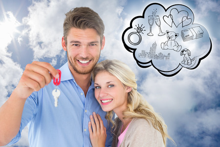 Attractive young couple showing new house key against bright blue sky with clouds photo