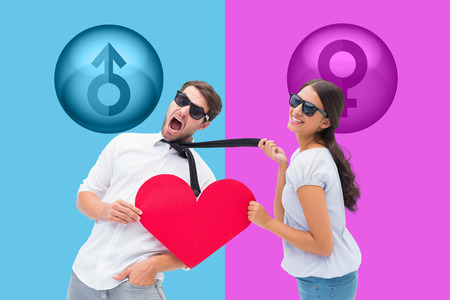 Brunette pulling her boyfriend by the tie holding heart against pink and blue photo