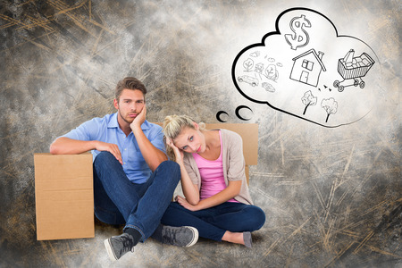 Unhappy young couple sitting beside moving boxes against life thoughts photo