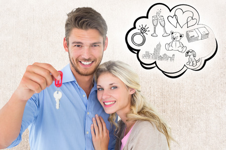 Attractive young couple showing new house key against weathered surface photo