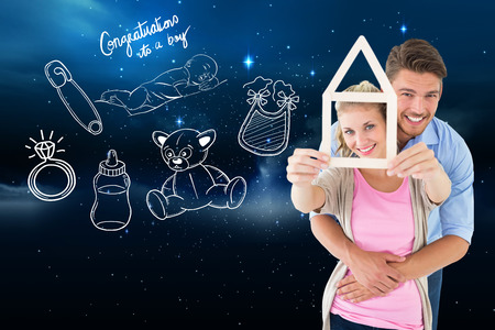 Young couple hugging and holding house outline against stars twinkling in night sky photo