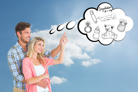 Attractive young couple embracing and pointing  against cloudy sky photo