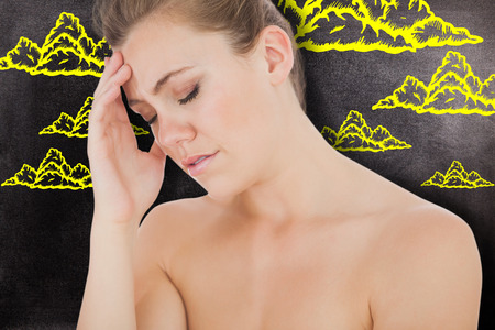 wincing: Woman with headache against black background Stock Photo