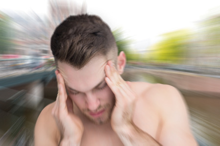 Man with headache against canal in amsterdam Stock Photo