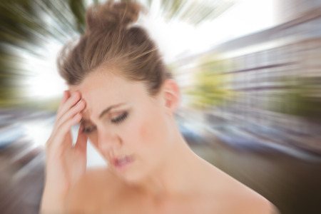 wincing: Woman with headache against canal in amsterdam Stock Photo