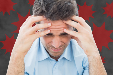 wincing: Man with headache against explosion Stock Photo