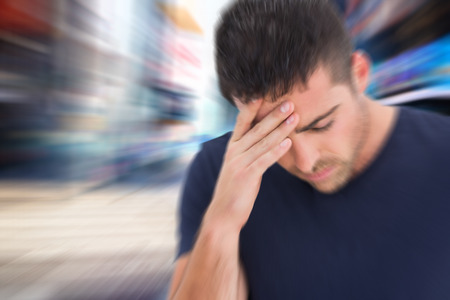 wincing: Man with headache against blurry new york street