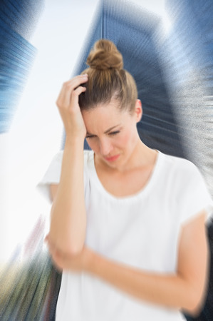 wincing: Woman with headache against skyscraper in city Stock Photo