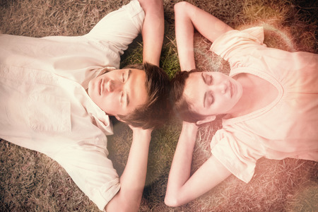 arms behind head: Man and a woman with their eyes closed lying head to head with both of their arms resting behind their neck on the grass