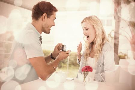 matrimonio feliz: El hombre propone matrimonio a su novia sorprendida rubia en la terraza del café en un día soleado