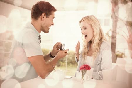 Man proposing marriage to his shocked blonde girlfriend on the cafe terrace on sunny day photo