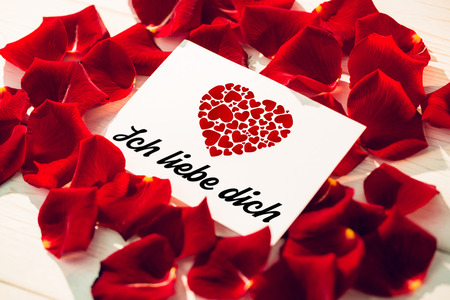 Liebe: ich liebe dich against card surrounded by rose petals