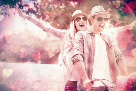 parejas felices: Pareja joven de la cadera va a dar un paseo en bicicleta en un día soleado en la ciudad