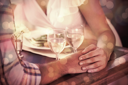 night table: Couple holding hands at dinner at home in the dining room