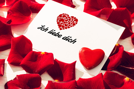 Liebe: ich liebe dich against card with red rose petals Stock Photo