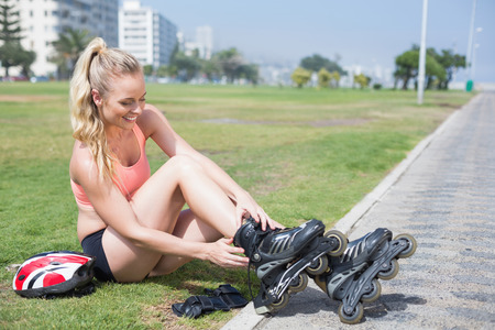 roller blade: Fit blonde getting ready to roller blade on a sunny day