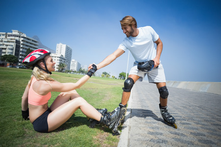 roller blade: Fit couple getting ready to roller blade on a sunny day Stock Photo