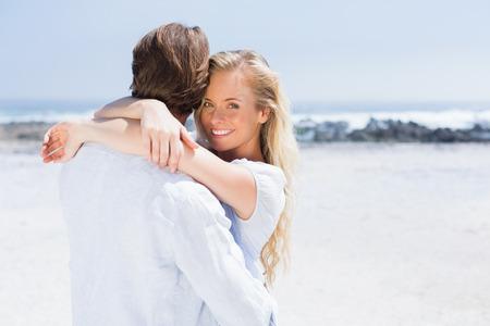 sunny day: Linda pareja abraz�ndose en la playa en un d�a soleado