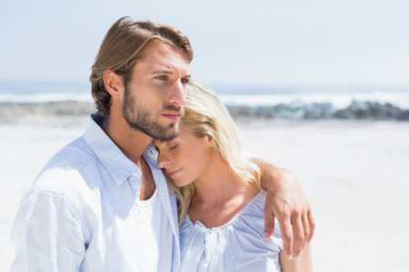 Cute couple hugging on the beach on a sunny day