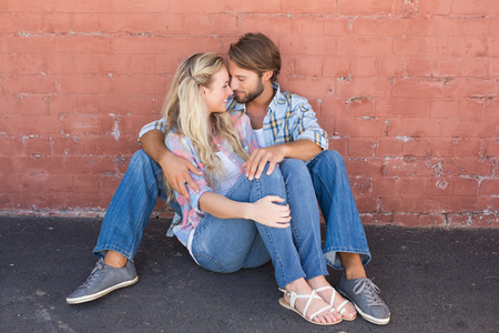 hugging couple: Attractive couple sitting on ground on a sunny day in the city Stock Photo