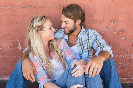 couple cuddling: Attractive couple sitting on ground on a sunny day in the city Stock Photo